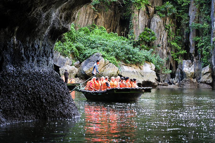 Tourist visit luon cave by bamboo boat